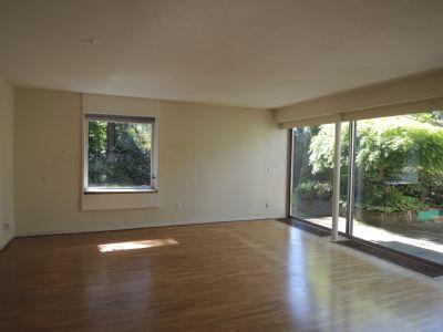 Das Wohnzimmer mit Parkettboden und Gartenblick ..