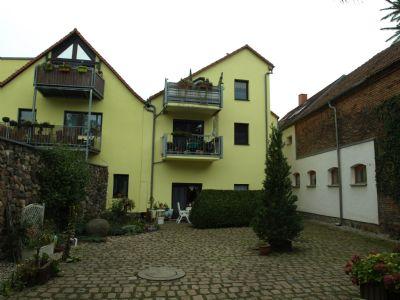 Rückansicht mit Balkonen und Terrasse und Ausfahrt