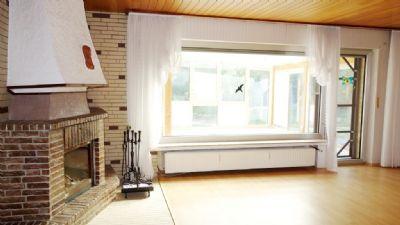 Wohnraum mit Kamin und Wintergarten
